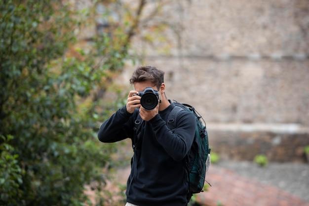 디지털 카메라를 사용하는 남성 여행자