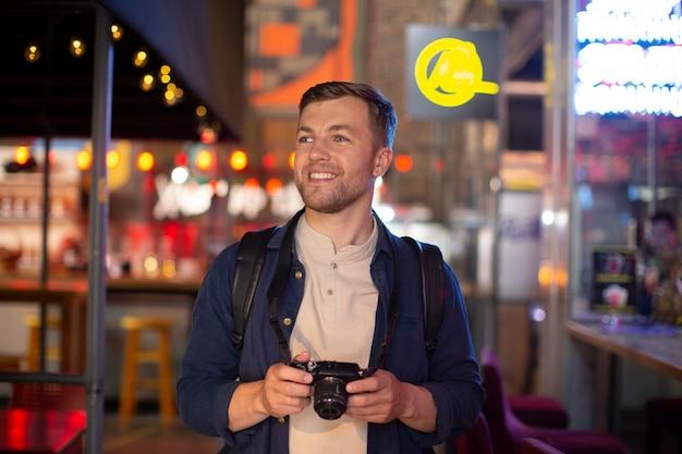 地元の場所でカメラを持っている男性旅行者
