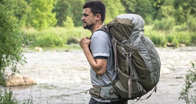 Путешественник-мужчина с большим походным рюкзаком у реки.