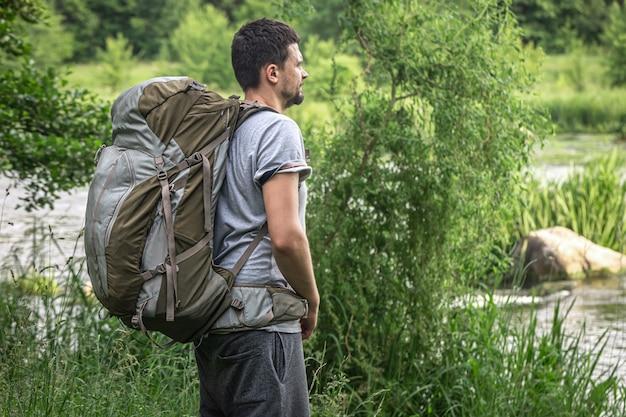 강 근처에 큰 하이킹 배낭을 메고 있는 남성 여행자.