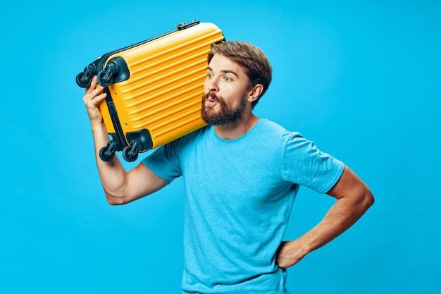 Мужской путешественник с чемоданом в руках позирует, отпуск