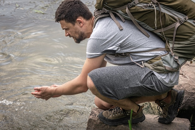 A male traveler with a large hiking backpack drinks water from a mountain river.