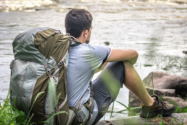 A male traveler with a large hiking backpack sits resting near the river.