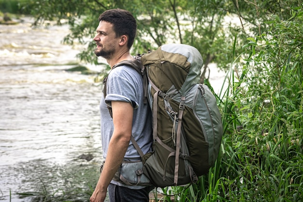A male traveler with a large hiking backpack stands near the river.