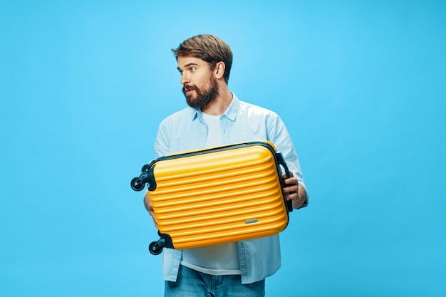 Male traveler with a suitcase in his hands posing in studio, vacation