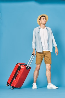 Male traveler with a suitcase ready to go on vacation, posing on blue with a red suitcase