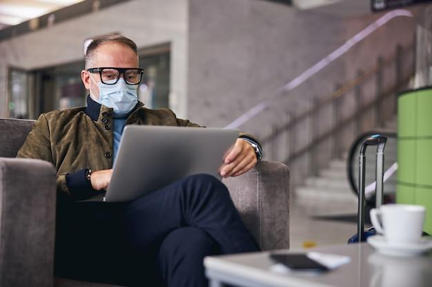Путешественник мужского пола, работающий на ноутбуке в гостиной