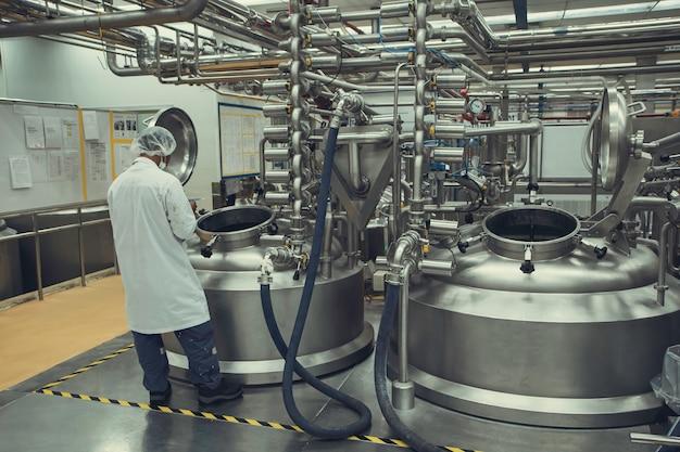 男性の2つの作業操作は、垂直ステンレス鋼タンク工場で粉乳セラーを処理します