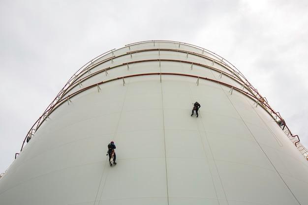 남성 2명의 작업자가 높이 탱크 쉘 플레이트 로프 사다리에 접근하여 두께 저장 탱크 가스 프로판의 안전 검사를 합니다.