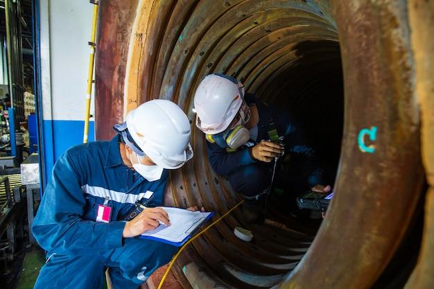 男性の2人の作業員による検査では、ボイラースキャンのコイルパイプの円形の厚さを危険な限られたスペースに測定しました。