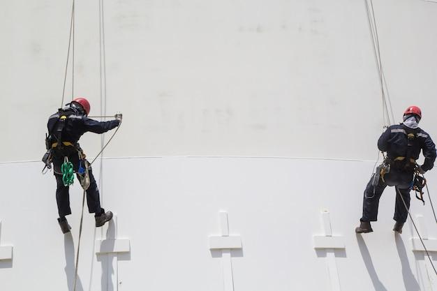 厚さ貯蔵プロパンホワイトタンク産業の男性2人労働者ロープアクセス検査
