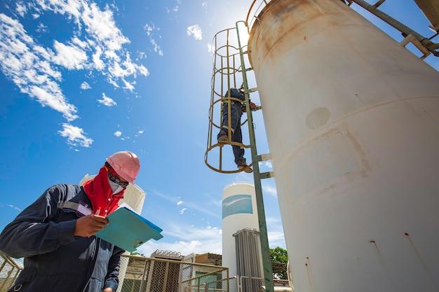 はしごの上の男性2人の作業員は、貯蔵タンクの化学薬品の超音波厚さシェルプレート上部を検査するためのものです。