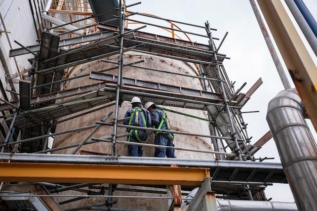 安全第一ハーネスを着用し、トップタンクオイルの高い足場の場所で作業している男性2人の労働者