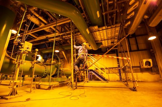 男性のアップモーションブラーが階段の足場検査パイプライン水力送電変電所と発電所を登る