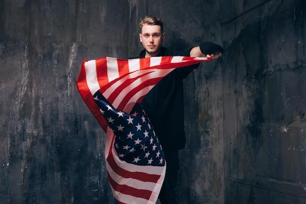 Мужчина-патриот сша с развевающимся национальным флагом