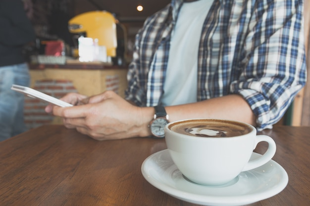 Male using a smart phone with coffee cup on wooden table.