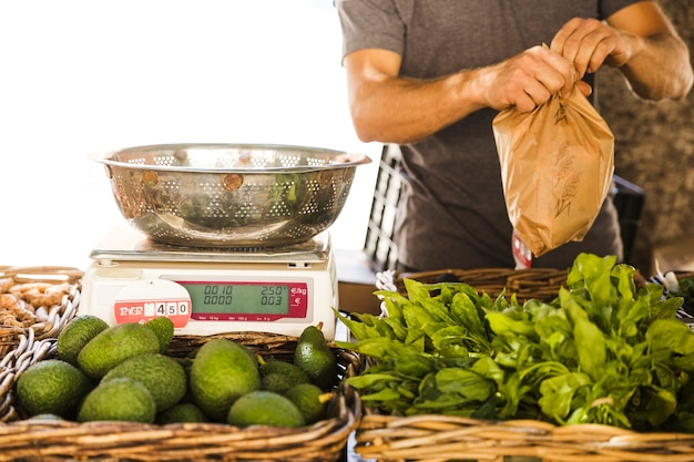 Мужской продавец овощей упаковки овощей для клиента на рынке