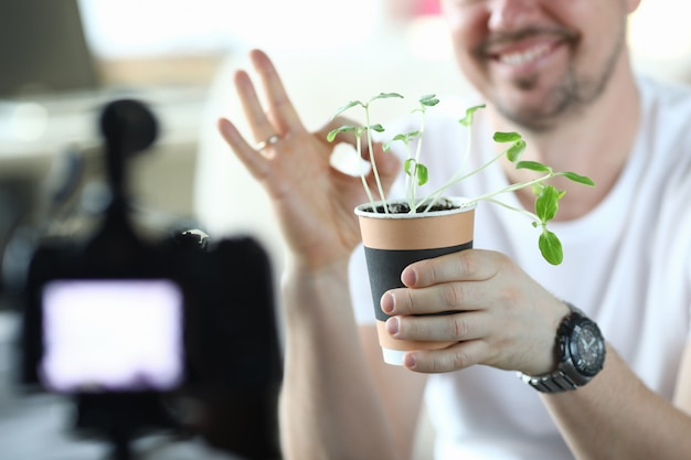 Male video blogger holding pot with green sprouts