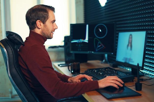 Мужчина-видеооператор редактирует и обрезает кадры и звук на своем персональном компьютере