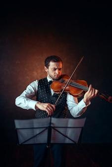 男性バイオリニストがバイオリンでクラシック音楽を演奏します。楽器を持つバイオリン男