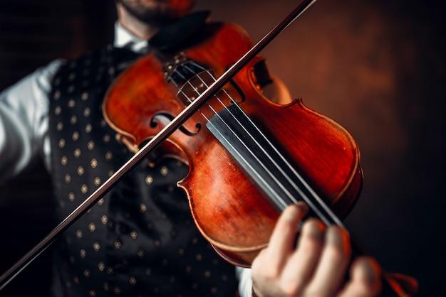男性バイオリニストがバイオリンでクラシック音楽を演奏