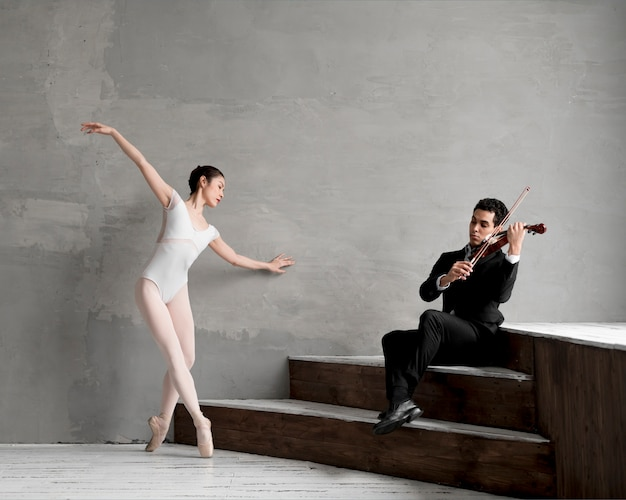 Male violinist playing music while ballerina dances