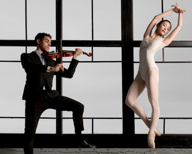 Мужской скрипач играет музыку в то время как балерина позирует