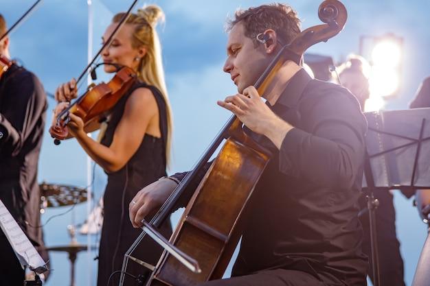 Виолончелист мужского пола играет в оркестре на концерте под открытым небом