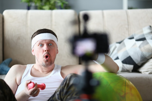 Male vlogger holds dumbbells in his