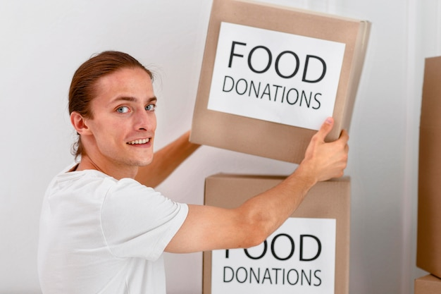 자선을위한 음식이 담긴 상자를 다루는 남성 자원 봉사자