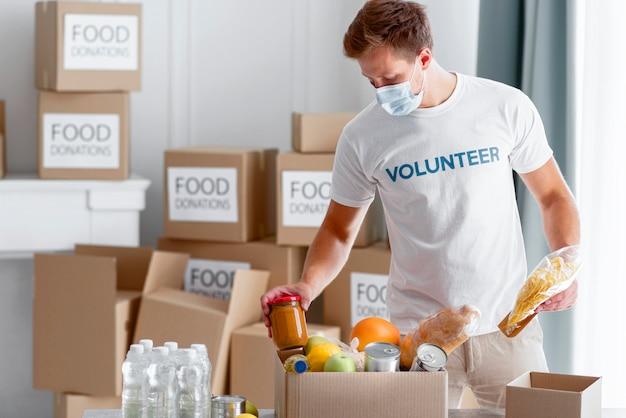 Волонтер-мужчина помогает упаковывать еду для пожертвования