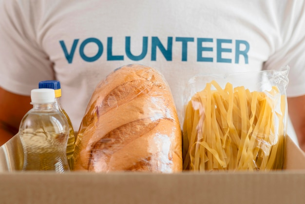 Мужской волонтер держит коробку с продуктами для благотворительности