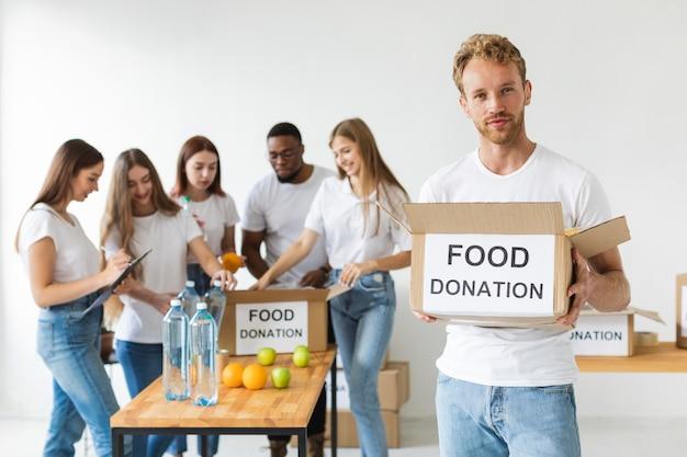 Волонтер-мужчина держит пожертвования на еду