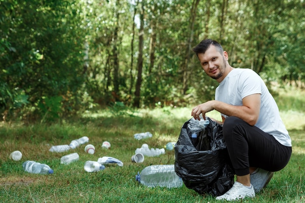 A male volunteer holding a garbage bag collects plastic.