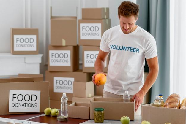 Волонтер-мужчина готовит коробки с едой для благотворительности