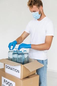 Волонтер-мужчина готовит бутылки с водой для пожертвования