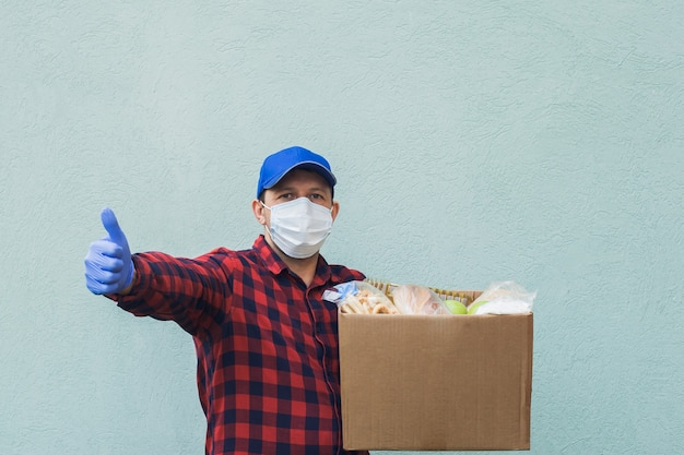 Male volunteer wearing a protective mask with a box of groceries, charity.