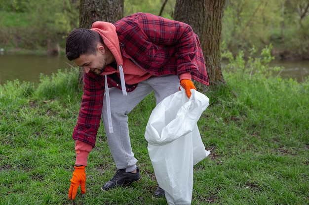 A male volunteer with a garbage bag cleans up the environment in the forest