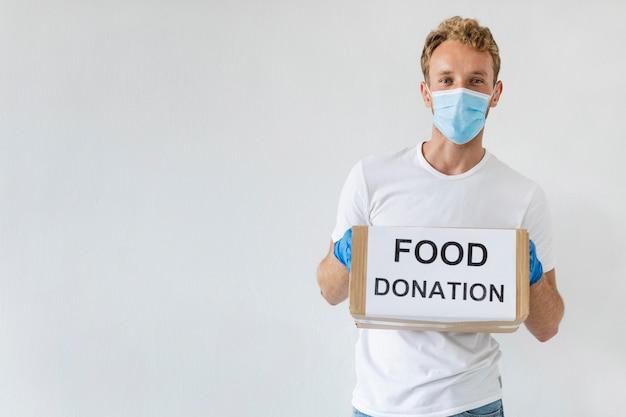 Мужчина-волонтер с медицинской маской и перчатками держит ящик для пожертвований
