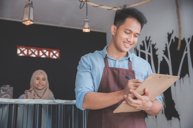 Male waiter in apron writing order