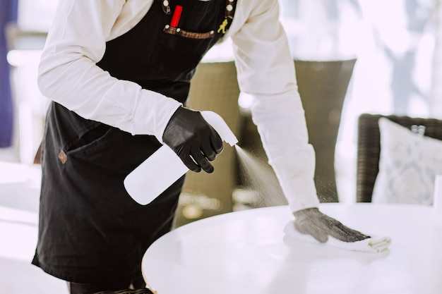 Male waiter in black apron, medical mask and gloves cleaning white table at the restaurant by disinfection bottle.
