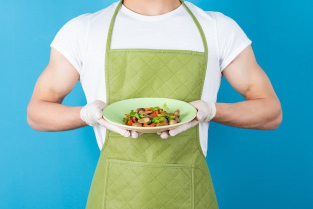 Male waiter in green apron holding delicious meal on blue wall