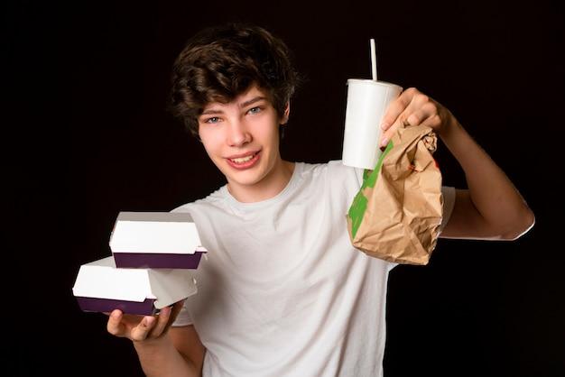 男性ウェイターは、暗い背景に分離されたハンバーガーと紙のフードボックスとファストフードソーダボックスを保持しますb