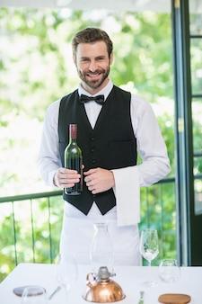 Male waiter holding bottle of wine