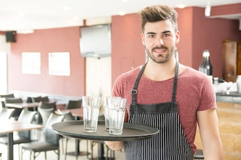 Male waiter holding tray with empty glasses in the bar