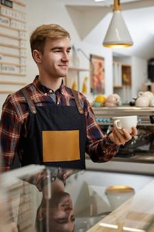 Официант-мужчина в фартуке держит чашку горячего напитка