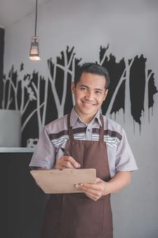 Мужской официант в порядке написания фартук