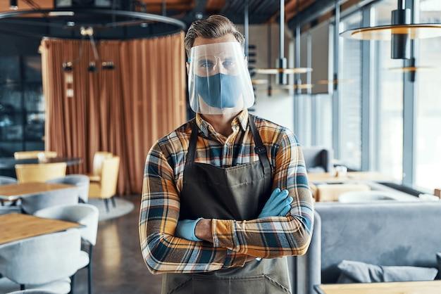 Официант-мужчина в защитном маске для лица, скрестив руки и стоя в ресторане