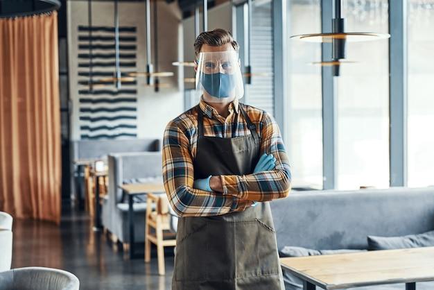 Официант-мужчина в защитной спецодежде, скрестив руки и стоя в ресторане