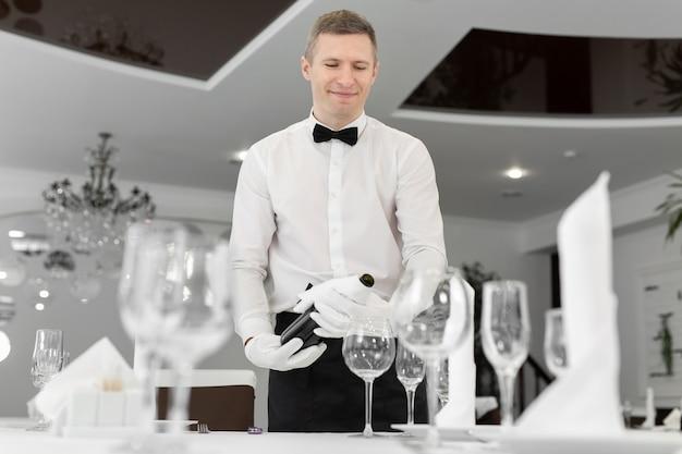 Официант-мужчина в белых перчатках наливает красное вино в бокал.